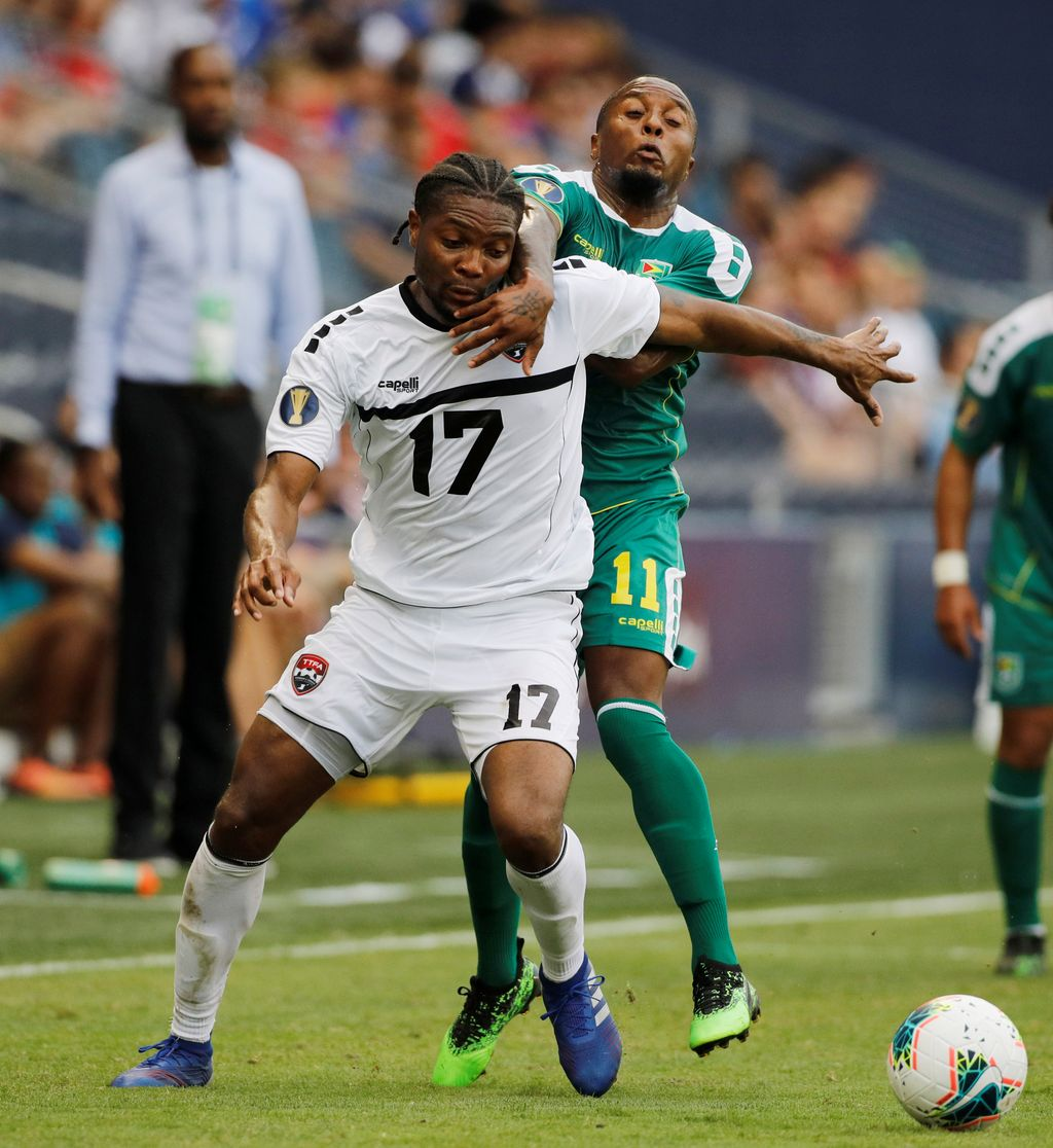 T&T's defender Mekeil Williams (17) is held back by Guyana midfielder Callum Harriott (11) as they battle for control of the ball during the second half of a CONCACAF Gold Cup football match in Kansas City, Kan., yesterday. (AP)