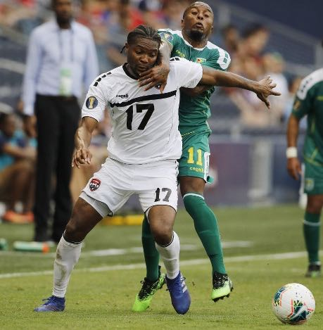 Photo: Trinidad and Tobago defender Mekeil Williams (foreground) is held back by Guyana midfielder Callum Harriott during Gold Cup action on 26 June 2019. (Copyright AP Photo)