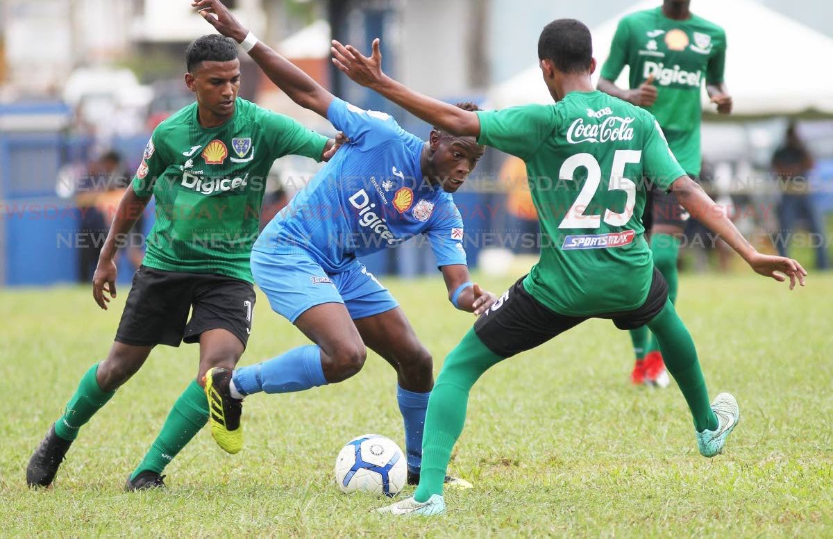 Naparima College player Decklan Marcelle (C) tries to evade Symron Wiseman(R) of St Bendict's College,during the Secondary Schools Football League match,held at Lewis Street, San Fernando,yesterday.