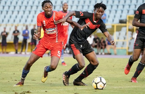 Caledonia's Tev Lawrence (L) vies with a Phoenix player for he ball during match day 3 of the TT Pro Legue First Citizens Cup 2019 between Morvant Caledonia and Phoenix FC, at the Hasely Crawford Stadium, Port of Spainnon Sunday. - Daniel Prentice/CA-images