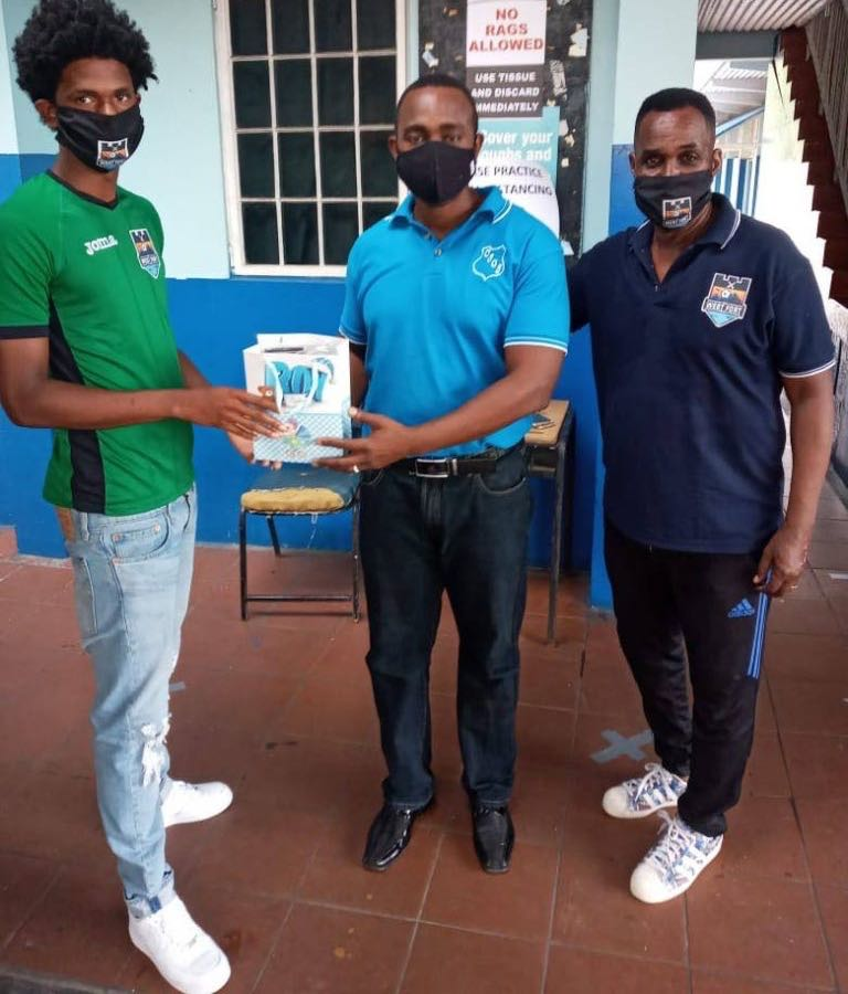 Real West Fort United and national pool player Jahiem Mc Fee, left, presents a Crystal Stream Government Primary School teacher with protective masks for SEA students. At right is club technical director Ron La Forest -