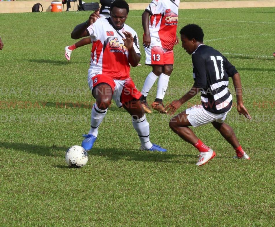 T&T footballer Sean Bonval, right, puts pressure on Jahiem Harry of the Tobago XI in a TT practice match at the St James Police Barracks in St James, on Saturday. PHOTO BY SUREASH CHOLAI - Sureash Cholai