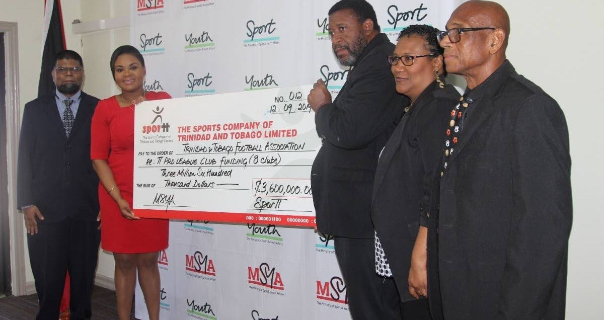 Shamfa Cudjoe, Minister of Sport and Youth Affairs, second from left, presents a cheque to David John-Williams, president of the TTFA. Looking on from left are Farook Hosein, permanent secretary, Ministry of Sport and Youth Affairs, Julia Baptiste, TTFA and Anthony Creed, Sport Company of TT.