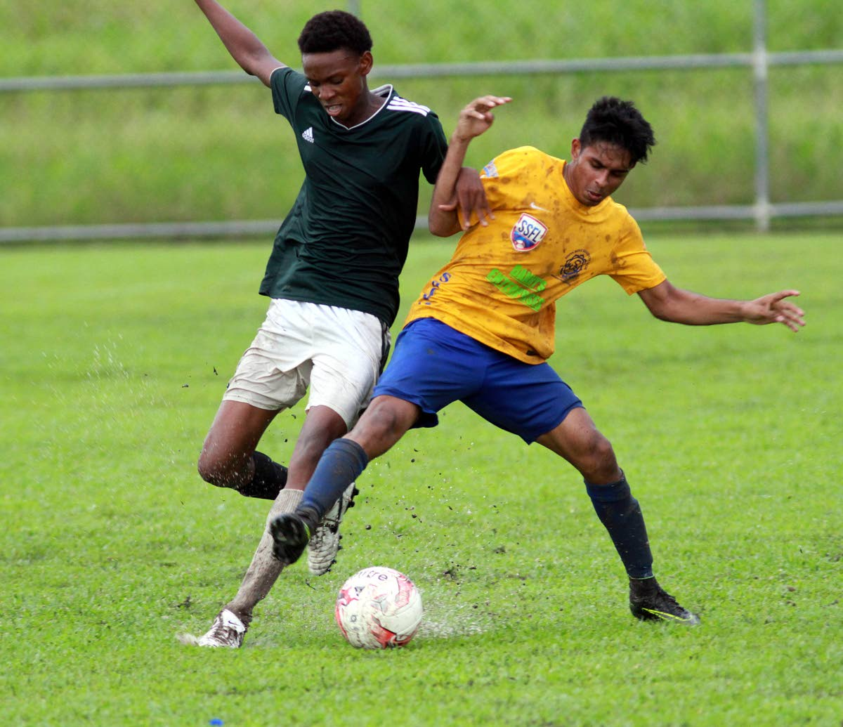 A Shiva Boys' player battles with his opponent from Rio Claro West during a SSFL South Zone Under-20 match on Friday at the Manny Ramjohn Stadium Training Ground, Marabella.
