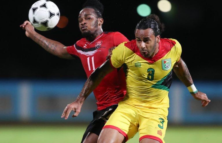 Guyana's Christopher Bourne, right, and Trinidad and Tobago's Neil Benjamin challenge for the ball in an international friendly at the Ato Boldon Stadium, Couva.