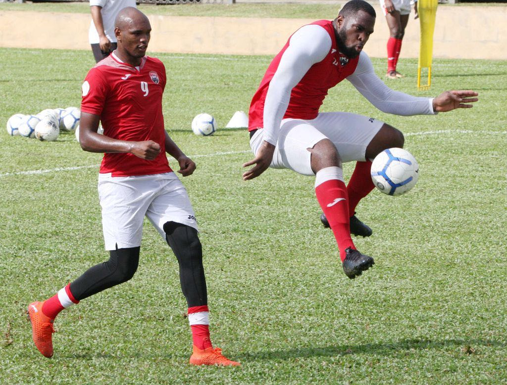 US-based T&T defender Josiah Trimmingham, right, attempts to control the ball while being closely watched by striker Brent Sam, as preparation for the T&T team heightens ahead of the World Cup Qualifiers in March, continued on Tuesday at the Police Grounds in St James. Trimmingham plays for USL League One club Madison FC. - ANTHONY HARRIS