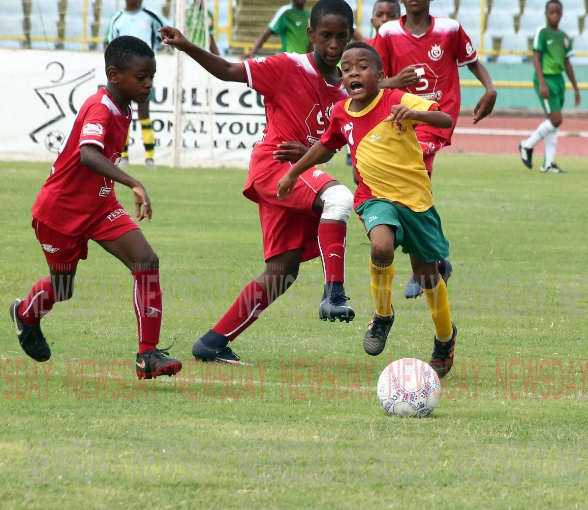 Trendsetter Hawks' Jaseem Celestine, right, runs with the ball in the Under-11 final, of the Republic Bank Cup National Youth League, against Pro Series, earlier today. Celestine was awarded the Most Valuable Player.