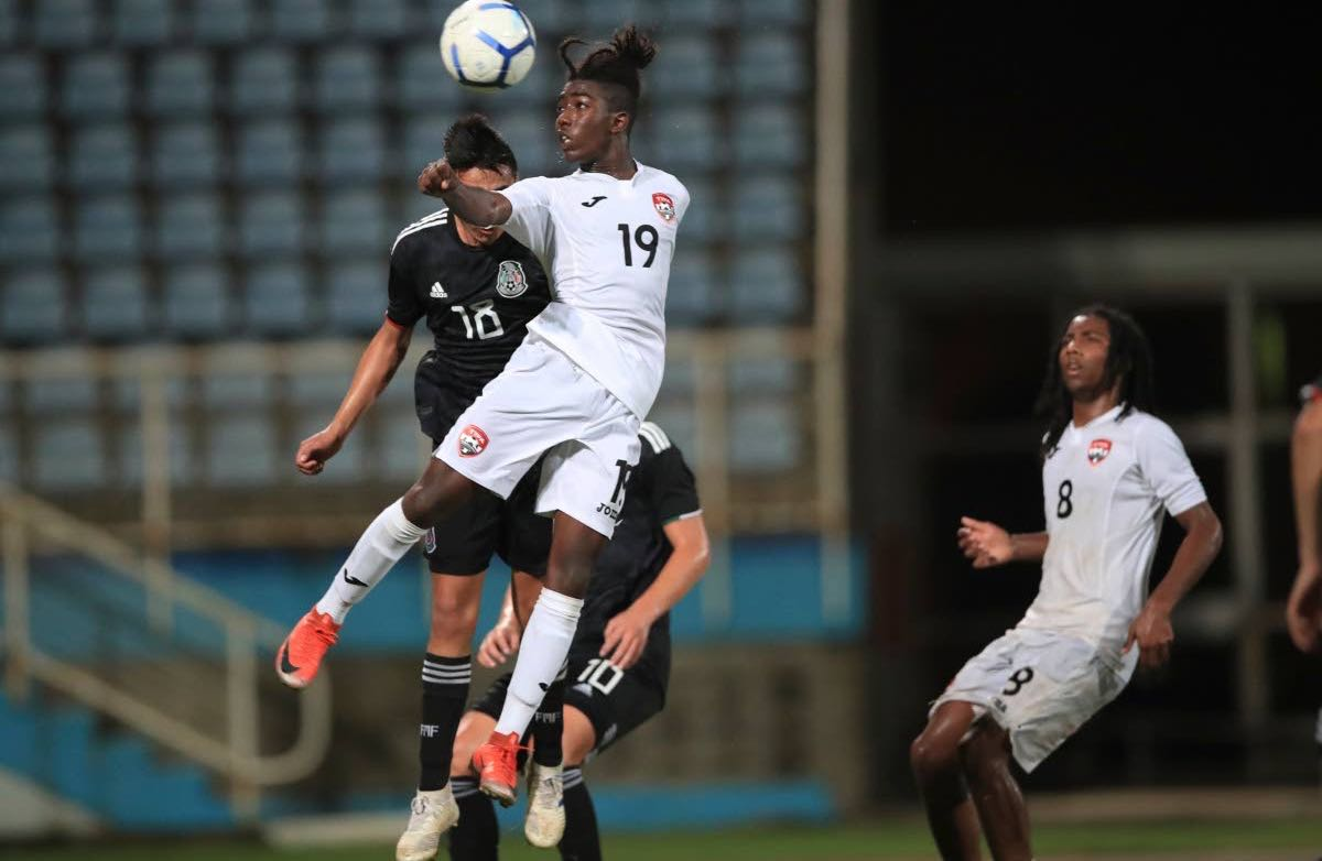 T&T's Isaiah Thompson (#19) attempts to steer a header towards goal, during day 3 match 2, of the TTFA Youth Invitational Tournament between TT and Mexico, at the Ato Boldon Stadium, Couva,on Sunday. Mexico won 4-1.