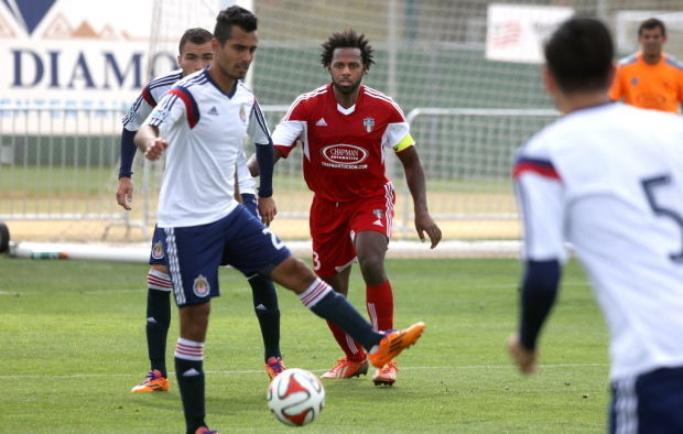 FC Tucson defender Kareem Smith, in red, guards against Chivas USA players in the second half of a Desert Diamond Cup game this week at Kino Sports Complex. Smith used his own frequent flier miles to travel to Tucson from Trinidad.