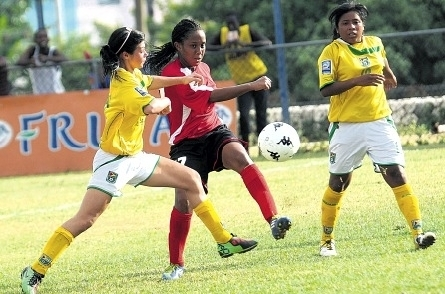 Guyana's Kailey Leila (left) challenges Trinidad's Jonnelle Warrick (centre) for a ball during their CFU Under-17 final-round World Cup qualifier at the Tony Spaulding Complex yesterday. Leila's teammate Ursuline Primus (right) looks on. T&T won the game, 8-0. (Photo: Jermaine Barnaby)